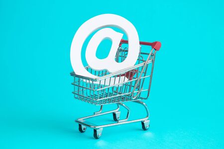 Email sign in shopping cart against blue background. Online shop minimal creative concept. 스톡 콘텐츠