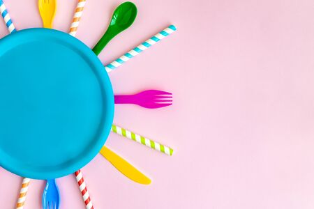 Top view of multicolored tableware and drinking straws abstract isolated on pastel rose. Space for copy.