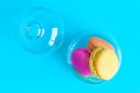 Flat lay of colorful macaroons in glass bowl against blue background minimal creative sweet food concept. 스톡 콘텐츠
