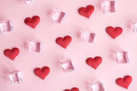 Flat lay of hearts and ice cubes pattern. Love and hate minimal creative concept.