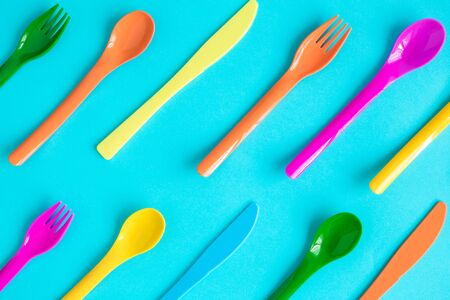Flat lay of colorful plastic cutlery against pastel blue background.