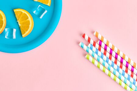 High angle view of drinking straws and plastic plate with ice cubes and orange fruit slices minimal creative beverage concept.