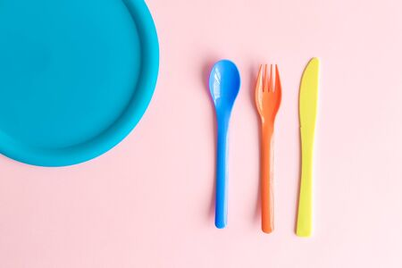 Flat lay of colorful spoon, fork and knife with plate abstract against rose background.