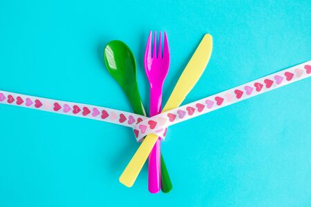 Flat lay of cutlery with heart design ribbon minimal food creative concept.