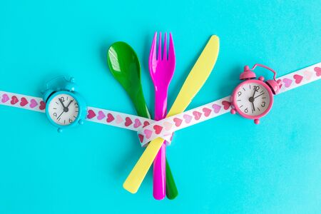 Flat lay of cutlery with heart design ribbon and alarm clocks minimal food creative concept. 스톡 콘텐츠