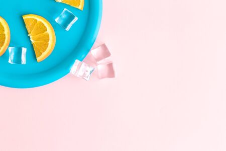 Flat lay of plastic plate with orange fruit slices and ice cubes against pastel pink background minimal creative concept. Space for copy.