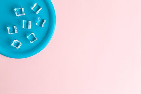 Flat lay of plastic plate with ice cubes against pastel pink background minimal creative concept. Space for copy. 스톡 콘텐츠