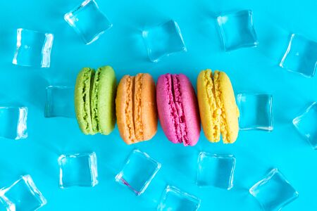 Flat lay of colorful macaroons and ice cubes against blue background minimal sweet food and drink creative concepts.