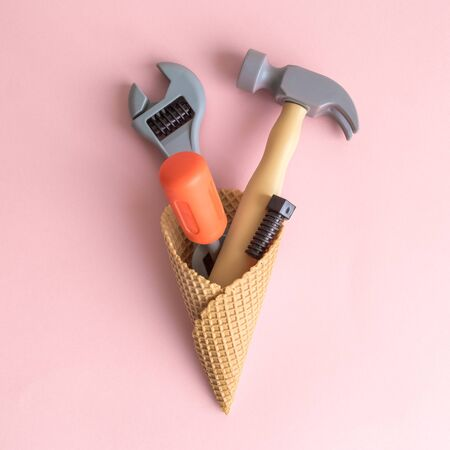 Set of carpentry tools in ice cream cone isolated on pastel pink background minimal creative concept.