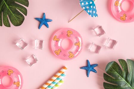 Flat lay of swimming floats, drinking straws,sea stars, monstera leaves, cocktail umbrella and ice cubes against pastel pink background minimal creative summer travel concept. 스톡 콘텐츠