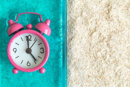 Flat lay of alarm clock in swimming pool or sea on sandy beach minimal creative summertime concept.