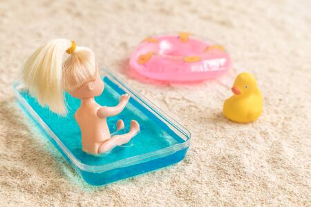 Girl sitting in small swimming pool for children on beach abstract. Inflatable pool float and rubber duck in sand. 스톡 콘텐츠