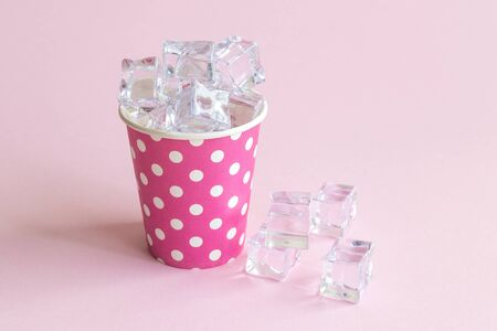 Paper cup polka design full of ice cubes against pastel pink background minimal creative refreshment concept. 스톡 콘텐츠