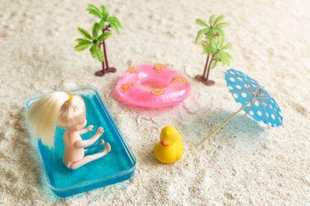 Baby doll enjoying sunny day at the beach minimal creative summer concept. 스톡 콘텐츠