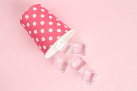 Flat lay of paper cup polka design with ice cubes against pastel pink background minimal creative refreshment concept. 스톡 콘텐츠