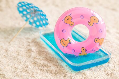 Kid pool with inflatable pool float and cocktail umbrella on sandy beach minimal creative summer vacation concept. 스톡 콘텐츠