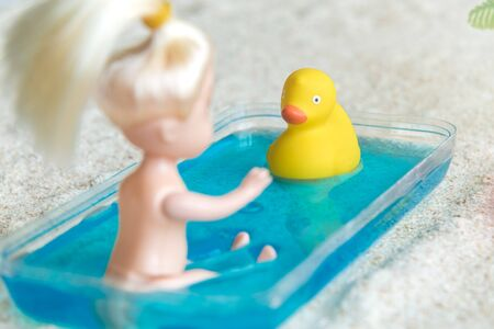 Baby doll bathing in kids swimming pool with rubber duck at the beach minimal creative summer concept.