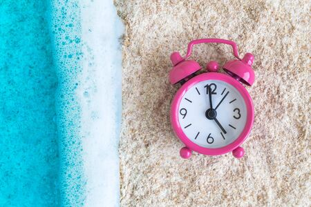 Flat lay of beautiful turquoise sea with waves and alarm clock on beach minimal creative summertime concept.