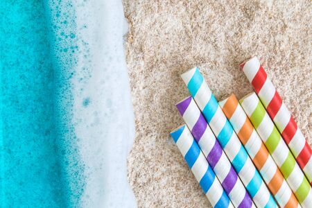 Flat lay of beautiful turquoise sea with waves and colorful drinking straws on beach minimal creative summertime concept.