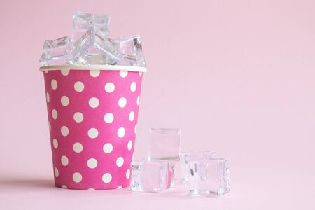 Disposable cup with ice cubes abstract isolated on pastel rose. 스톡 콘텐츠