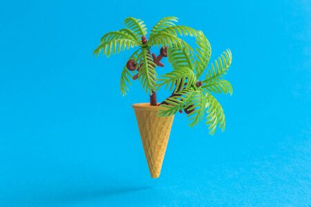 Ice cream cone with palm trees against pastel blue background minimal summer vacation tropical creative concept.