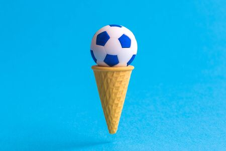 Ice cream cone with soccer ball against pastel blue background minimal summertime sweet food and sport creative concept.