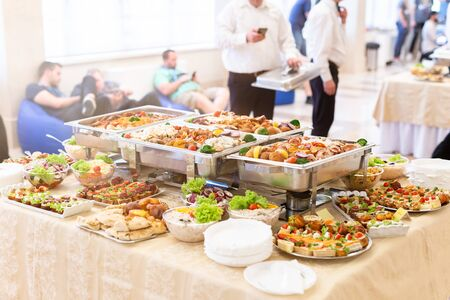 Catering buffet with food on table and waiters in the background. Reklamní fotografie