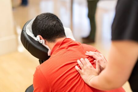 Man seated in a massage chair for back massage. Фото со стока