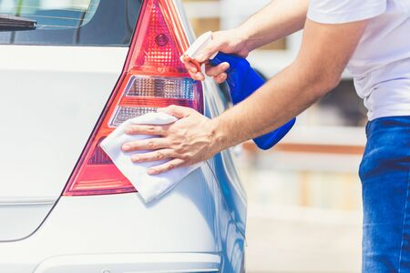 Close up of man cleaning rear part of the car with cloth and spray bottle, car maintenance concept. Foto de archivo