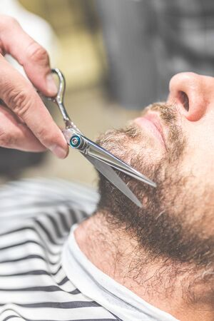 Close up of barber cutting beard of his client with scissors at barbershop. Stock fotó