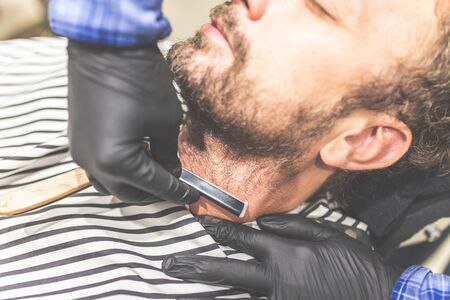 Close-up hands of barber holding razor and shaving a client. Stock fotó