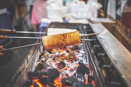 Chimney cake rolls spinning over hot coals at market stand. Standard-Bild - 131480113