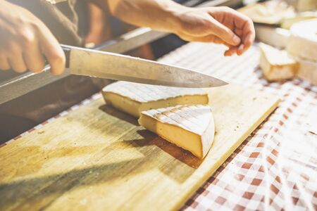 Cutting aged cheese on agricultural fair stand.
