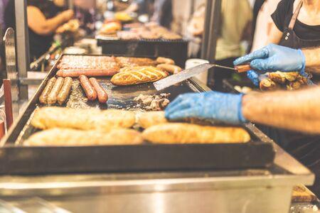 Close up of man preparing sausages on barbecue at street market festival. Reklamní fotografie