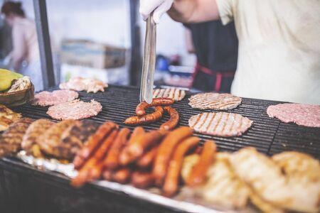 Man preparing burgers and sausages at street festival.