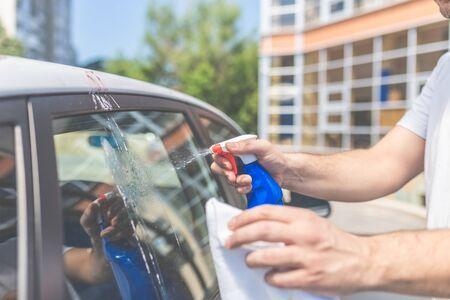 Cerca del hombre limpiando el coche con un paño y una botella de spray, el concepto de mantenimiento del coche. Mierda de pájaro, gota de mancha de pájaro en la ventana del coche, desperdicio sucio de pájaros que caen salpicaduras, primer plano de mierda de pájaro de mancha sucia, gota de caca de pájaro salpicado Foto de archivo