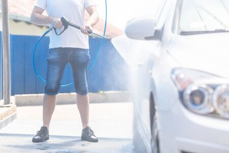 Man washing car wheel with high pressure machine for car wash 写真素材