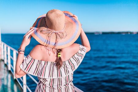 Cruise ship vacation woman enjoying travel vacation at sea. Free carefree happy girl looking at ocean and holding sunhat.