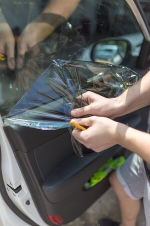 Process of removing sunlight protective car window glass foil. Reklamní fotografie