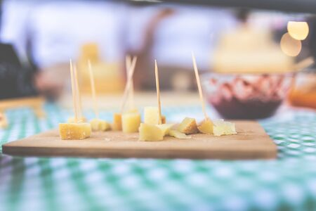 Close up of small cheese sample pieces with toothpicks on wooden cutting board. Stock fotó