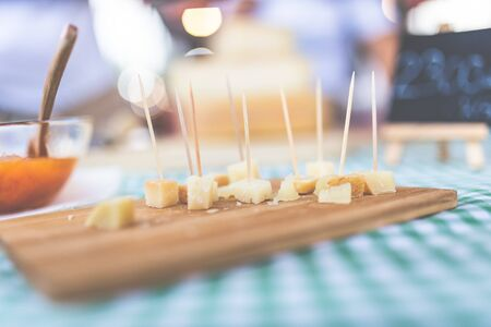 Cubes of traditional handmade cheese with toothpicks on street food market stand.
