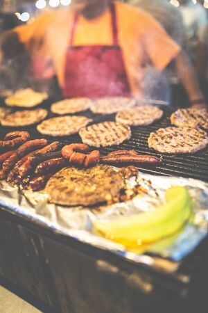 Street food barbecue burgers and sausages preparation. Fast food concept.