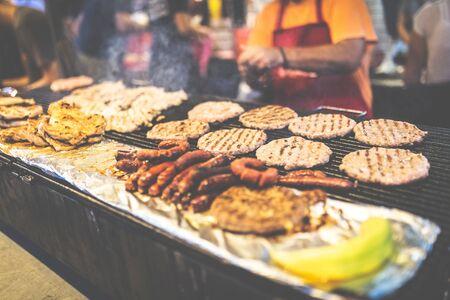 Chef preparing burgers and sausages at street festival. Reklamní fotografie