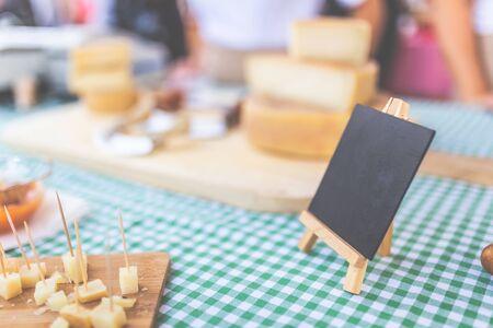 Soporte del mercado callejero de queso con tablero en blanco para copiar. Foto de archivo