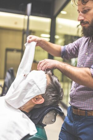 Hairdresser covering face of client with towel. Man visiting barber shop.