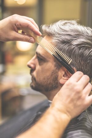 Barber cutting and modeling hair with scissors and comb.