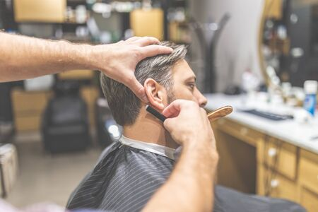 Making hair look magical. Side view of young bearded man getting shaved with straight edge razor by hairdresser at barbershop