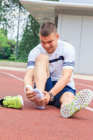 Jogger checking if his ankle is broken or twisted while sitting on running track.