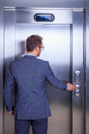 Businessman calling the elevator