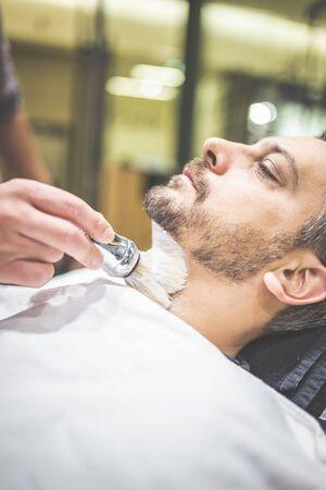 Professional hairdresser applying shaving foam on client skin in barbershop.